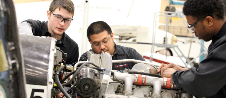 two miat technology students learning hands on working on an engine in in a technical career course shop